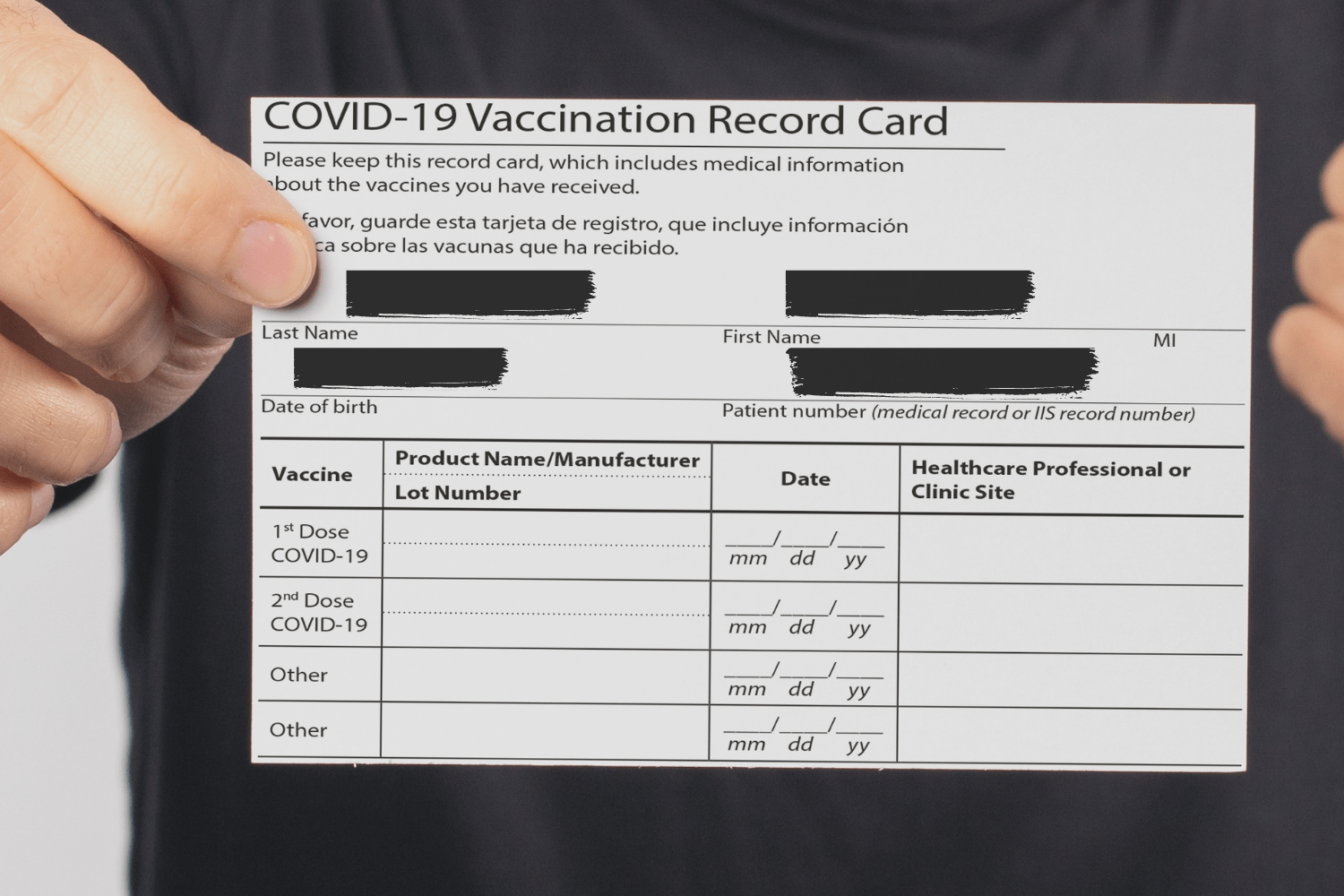 COVID-19 vaccination card with personal information blocked out.