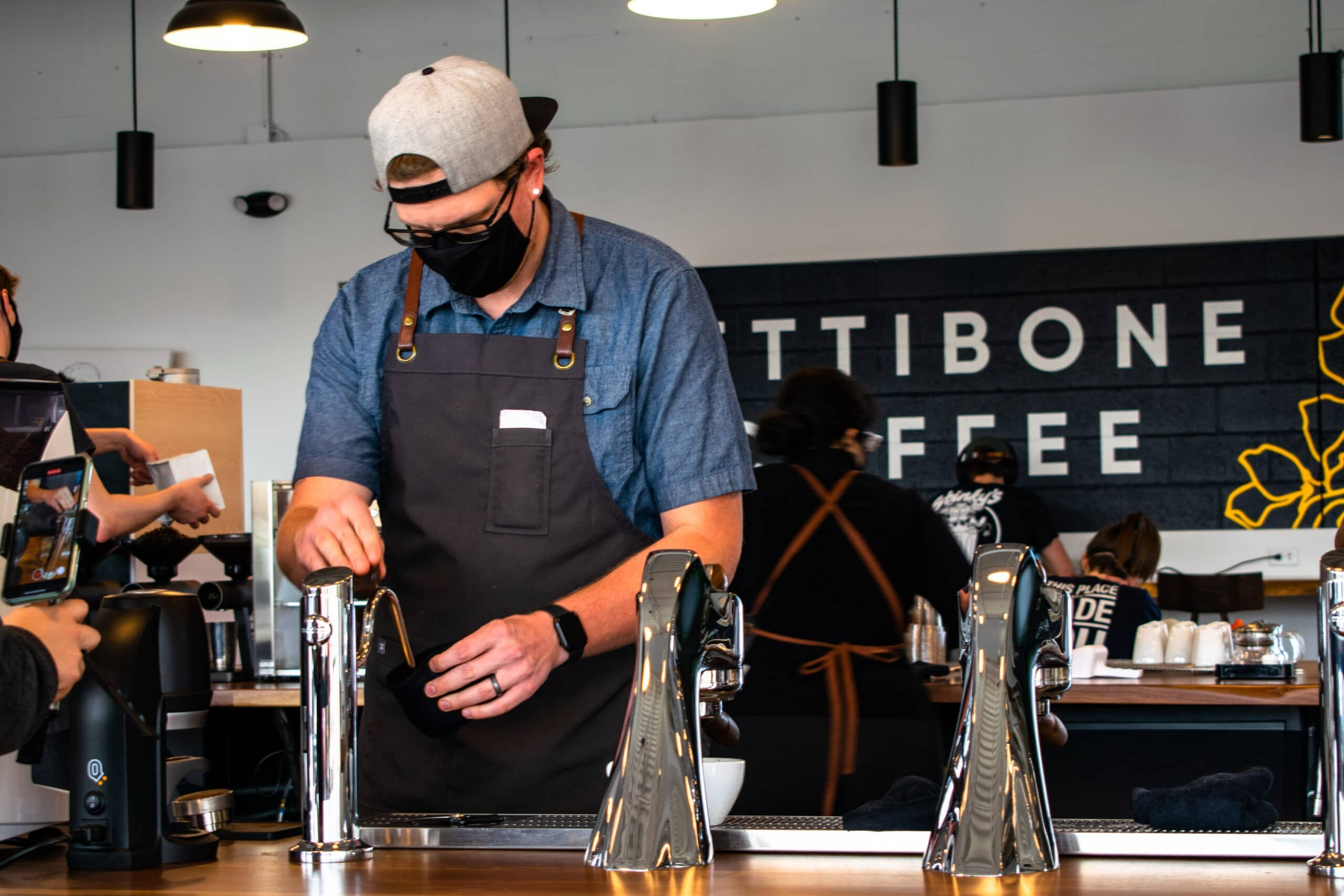 Barista at Pettibone Coffee preparing a latte.