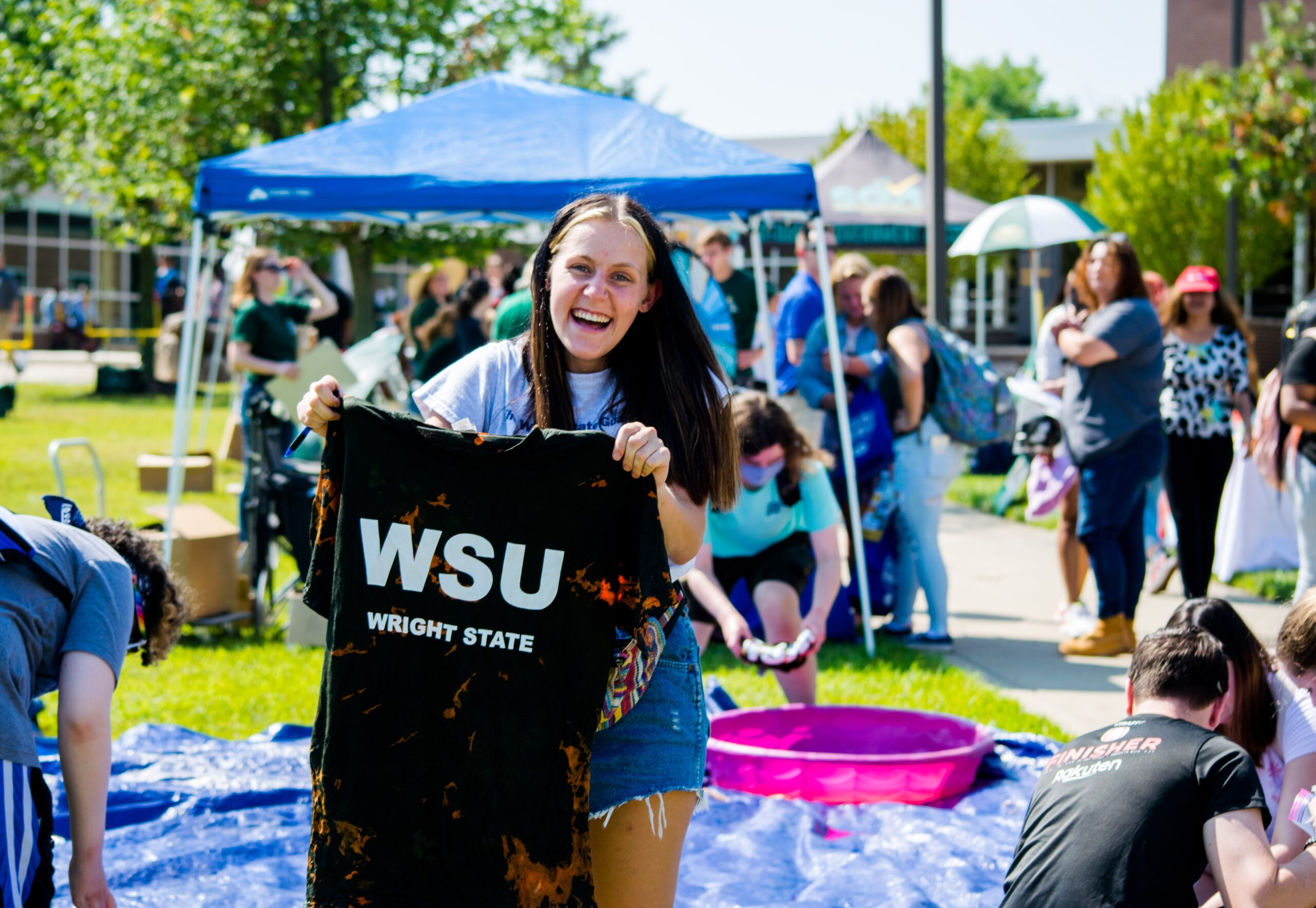 student holding up WSU t-shirt at fall festival